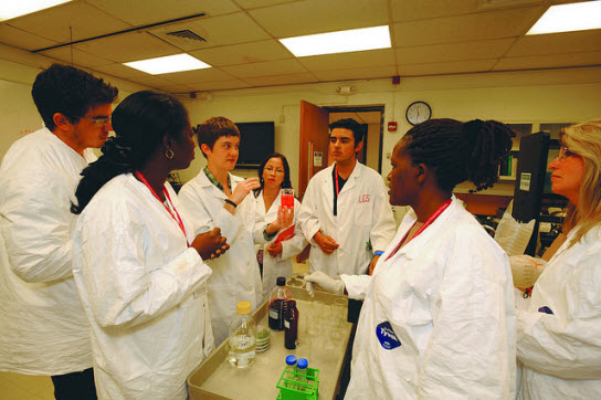 7 individuals in white lab coats in a plant pathology lab